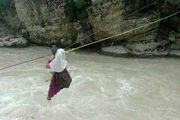 دانش آموزان این روستا با طناب به مدرسه می روند / آویزان شدن روی رودخانه خروشان برای درس خواندن ! +عکس